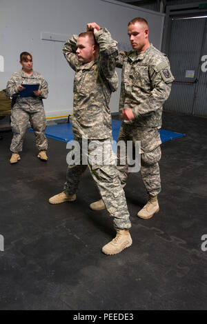 U.S. Army Sgt. Sterling Quimby, from 1st Battalion, 169th Aviation Regiment and assigned to Multinational Battle Group-East, walks through the steps of handling a detainee while being graded by Sgt. 1st Class Lahomma Fowler, from the 363rd Military Police Company, for the MNBG-E Soldier of the Month competition, Aug. 1, 2015, at Camp Bondsteel, Kosovo. The competition, held by Command Sgt. Maj. Ralph Johnson, the senior noncommissioned officer for the North Carolina National Guard's 30th Armored Brigade Combat Team as well as MNBG-E, was broken into two categories, one for junior enlisted Sold - Stock Photo