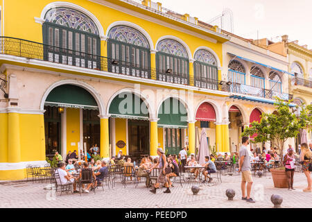 People in cafes and restaurants on Plaza Vieja, Old Havana, Cuba - Stock Photo