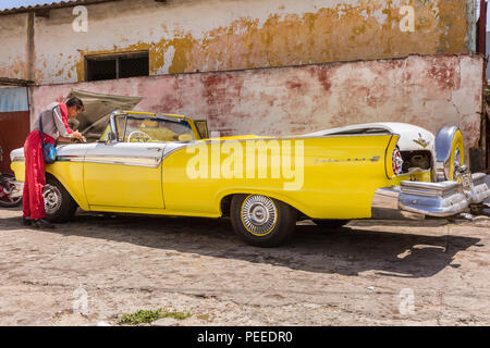 1957 Ford Fairlane 500 Skyliner convertible in yellow, American classic car, mechanic does repair and maintenance at a garage in Havana, Cuba - Stock Photo