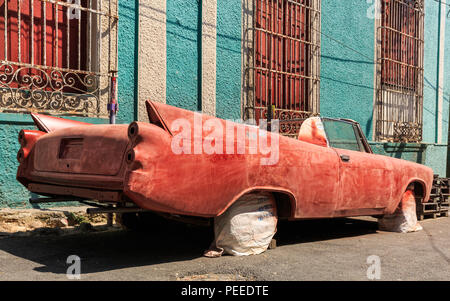 Old American classic car wreck, chassis being restored and re-painted in Havana, Cuba - Stock Photo