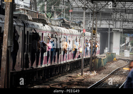 Passengers hanging out of trains door on a Mumbai Suburban Railway train at Bandra station in Mumbai, India - Stock Photo