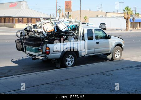 Silver colored Toyota Tundra with over loaded truck bed containing stacked chairs, bicycles, and other items. - Stock Photo