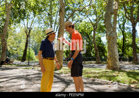 Colourfully dressed italian men both with straw hats meeting and greeting each other on a summers morning at the park. Piacenza, Italy. - Stock Photo