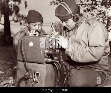 Navajo code talkers, cousins PFC Preston Toledo and PFC Frank Toledo, attached to a Marine Artillery Regiment in the South Pacific during World War II, use a field radio to transmit orders in their native Navajo tongue. Photo: July 7, 1943. - Stock Photo