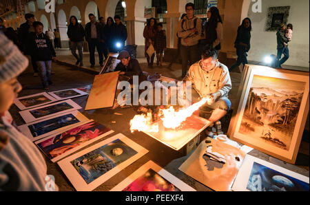 Cuenca, Ecuador / June 1, 2018: Street artists create elaborate paintings using only spray paint cans and fire in Cuenca, Ecuador - Stock Photo