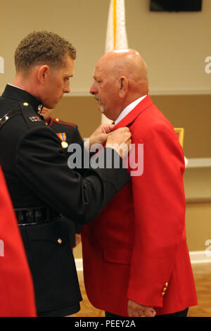 Capt. Connor Wentling, executive officer, Marine Corps Recruiting Station Columbia pins an eagle, globe and anchor on his father, John Wentling, during the Honorary Marine Ceremony held at the American Legion Post 34 on Aug. 8, 2015. Numerous letters of support from family members, Marines, congressmen, senators and a sponsorship from a general level officer started the process of him earning the title.