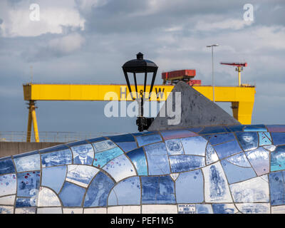 Belfast, Northern Ireland, UK -  August, 8, 2018: The Big Fish or Salmon of Knowledge with one of the Harland and Wolff shipyard cranes in the backgro - Stock Photo
