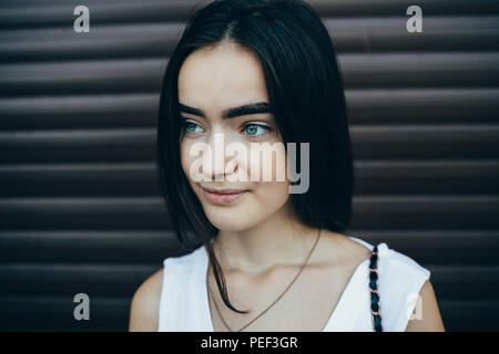Close-up portrait of happy pretty girl with long dark hair, big eyebrows and blue eyes. Female wearing white top standing over brown blinds background - Stock Photo