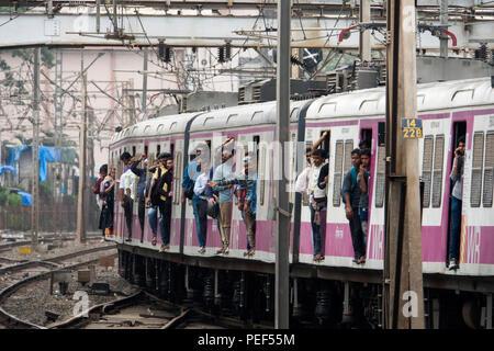 Passengers hanging out of trains door on a Mumbai Suburban Railway train arriving at Bandra station in Mumbai, India - Stock Photo