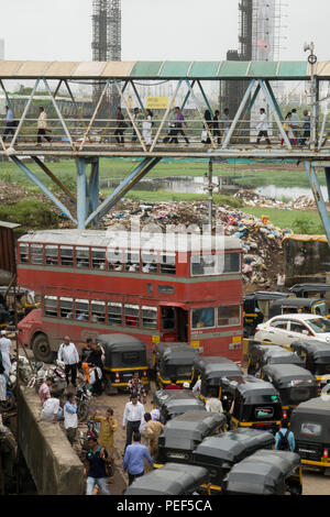 Double decker bus in traffic on Station road with Bandra pedestrian skywalk above, Mumbai, India - Stock Photo