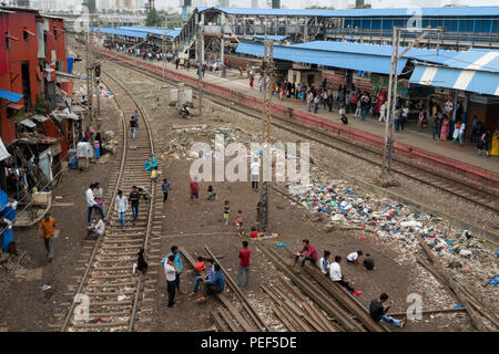 People from slum area with piles of plastic rubbish on tracks next to Bandra train station, Mumbai, Nepal - Stock Photo