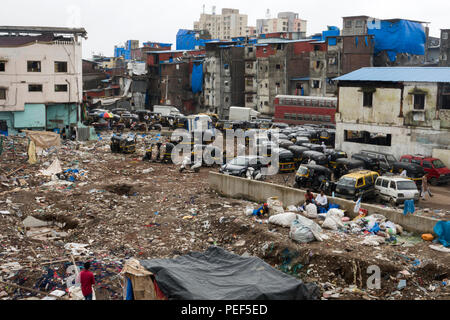 Slum area covered in trash with tuk tuk auto rickshaws waiting for passengers outside of Bandra railway station skywalk in Mumbai, India - Stock Photo