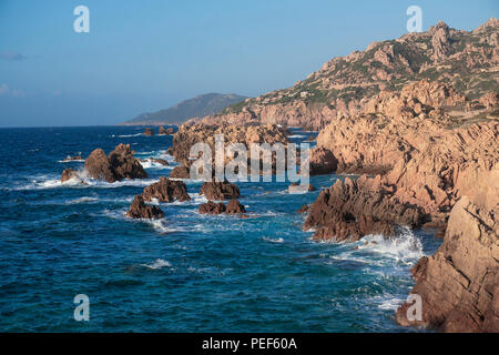 Reddish crumpled porphyry rocks at the rocky coast of Costa Paradiso, Sardinia, Italy - Stock Photo