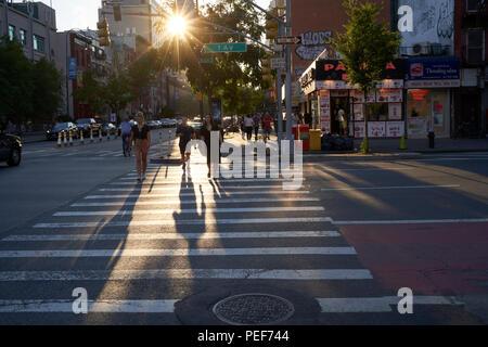 Pedestrians crossing street at crosswalk by sunset in Manhattan, NY - Stock Photo