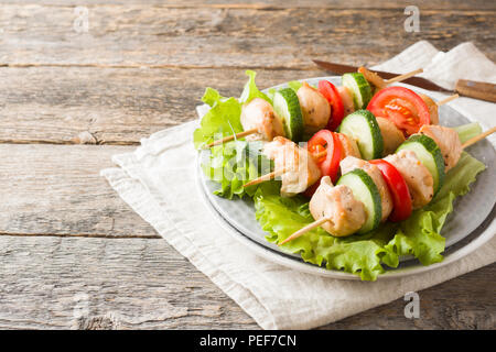 Traditional chicken kebab on wooden skewers with tomatoes, cucumbers and fresh herbs on a plate. - Stock Photo