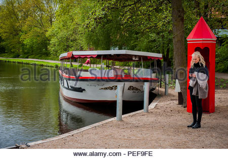 A woman checks her cell phone in Munke Mose Park in Odense. - Stock Photo