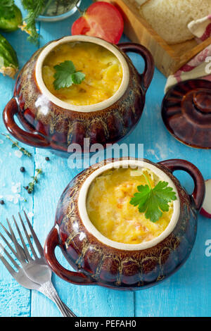 Potatoes and red fish with cream and cheese bake in clay pots in the kitchen wooden background. Russian cuisine. - Stock Photo
