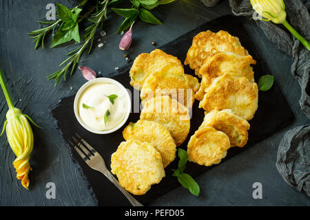 Vegan vegetable fritters on a background of slate cutting board. Fried vegetarian cutlets or pancakes. The concept of fast food. Top view flat lay bac - Stock Photo