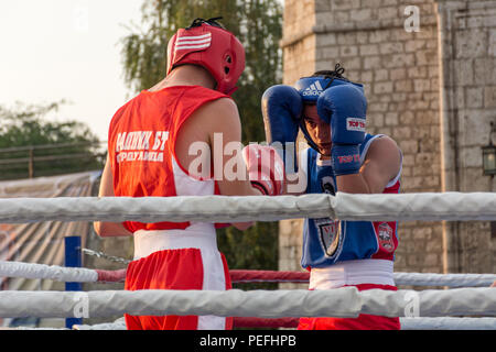 Nis, Serbia - August 14, 2018 Two young man boxing in ring outdoor in sunset. Fighters in protective gloves and cloths. Close up, selective focus - Stock Photo