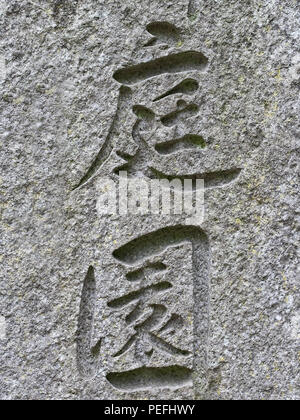 Japanese / Chinese letters signifying 'Garden' engraved on stone wall. - Stock Photo