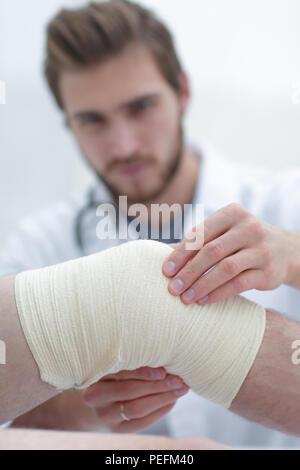traumatologist examining the bandage on his knee. - Stock Photo