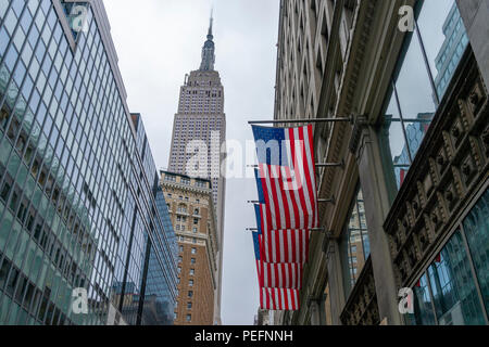 Empire State Building and American flags in New York City - Stock Photo