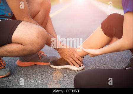 Ankle sprained. Young woman suffering from an ankle injury while exercising and running and she getting help from man touching her ankle. Healthcare a - Stock Photo