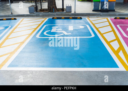 International handicapped (wheelchair) or Disabled parking symbol painted in bright blue on parking space. - Stock Photo