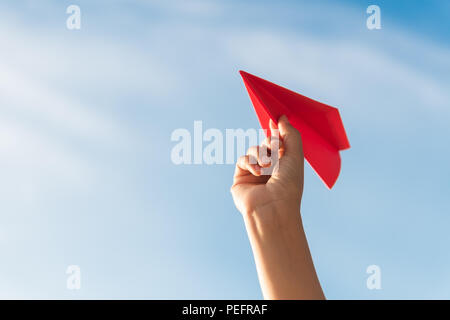 Woman Hand holding red paper rocket with blue sky background. freedom concept. - Stock Photo