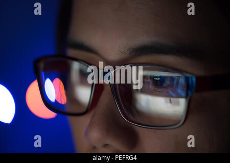 The image of computer screen in the glasess. Close up business woman wearing glasses working in the office on the laptop. - Stock Photo