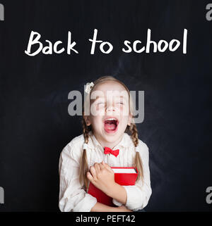 Pupil girl having fun because she goes to school for the first time. Child with school book. Back to school concept - Stock Photo