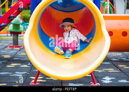 Close up happy little cute girl having fun and sliding on outdoor playground. - Stock Photo