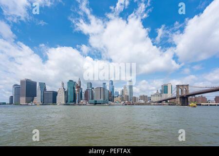 Manhattan skyline and Brooklyn Bridge in daytime - Stock Photo