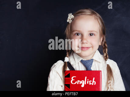Little girl student with english book near blackboard in the classroom. Learn language and education concept. - Stock Photo
