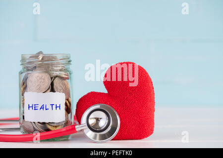 Money saving and health care concept. A jar contains coins with stethoscope and handmade red heart on white and pastel green wooden background. - Stock Photo