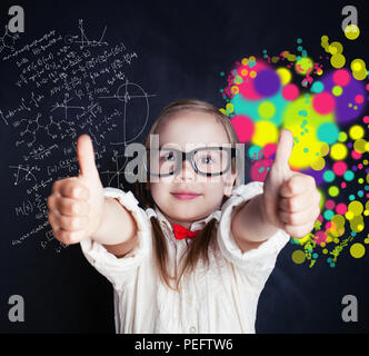 Little genius girl on chalk board in classroom with symbol of right and left hemispheres of the brain - science and arts elements - Stock Photo