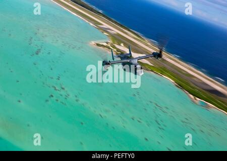 PACIFIC OCEAN – An MV-22B Osprey from Marine Medium Tiltrotor Squadron 166 Reinforced, 13th Marine Expeditionary Unit (MEU), flys over Wake Island, during a regularly scheduled deployment of the Essex Amphibious Ready Group (ARG) and the 13th MEU, August 1, 2018. The Essex ARG/ 13th MEU is a is a capable and lethal Navy-Marine Corps team deployed to the 7th fleet area of operations to support regional stability, reassure partners and allies and maintain a presence postured to respond to any crisis ranging from humanitarian assistance to contingency operations.  (U.S. Marine Corps photo by Cpl. - Stock Photo