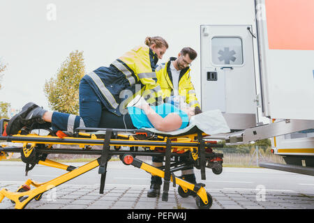 Emergency doctor taking care of seriously injured woman - Stock Photo