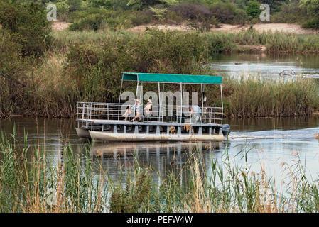 tourist boat on the okavango river in namibia. - Stock Photo