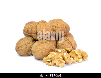 Horizontal photo of couple of walnut kernels in front of pile of walnut shells isolated on white background. Healthy and tasty snacks. - Stock Photo