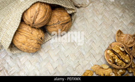 Horizontal photo of beautiful arrangement of walnut shells in burlap sack and walnut kernels on light wicker surface. Available copy space in middle o - Stock Photo