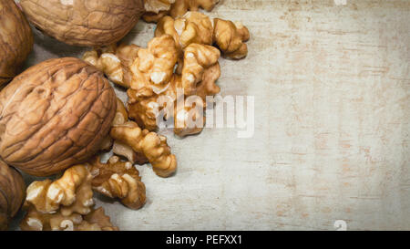 Horizontal close up photo of mix of walnut shells and walnuts kernels on light wooden surface, with space for copy. - Stock Photo