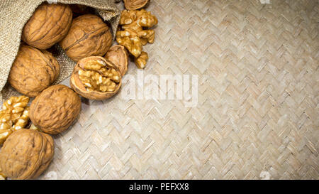 Horizontal photo of an arrangment of walnuts shells and walnut kernels in burlap sack on light wicker surface, with space for copy. - Stock Photo