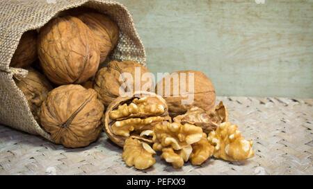 Horizontal photo of walnut shells and walnut kernels bursting out of burlap sack on wicker surface. - Stock Photo