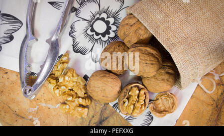 Horizontal photo of walnut shells and kernels in burlap sack on marble surface with white towel with flowers. Nutcracker next to walnuts. - Stock Photo