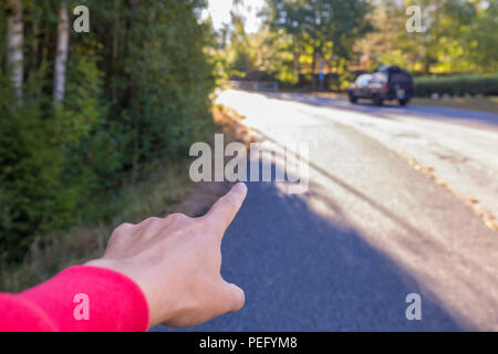 Person's hand and index finger pointing straight ahead on a street, giving directions - Stock Photo