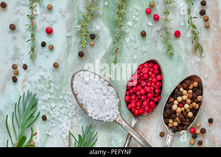 Herbs with salt and pepper in spoons on marble stone background, top view, flat lay. Rosemary, thyme, salt and mixed peppercorns in vintage metal spoo - Stock Photo