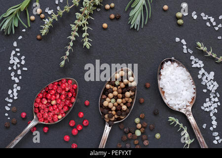 Herbs with salt and pepper in spoons on black slate stone background, top view, flat lay. Rosemary, thyme, salt and mixed peppercorns in vintage metal - Stock Photo