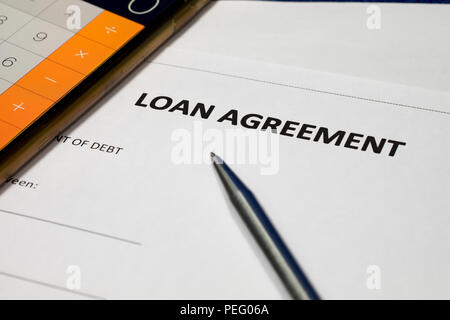 Loan agreement form document, stainless steel pen and calculator. - Stock Photo