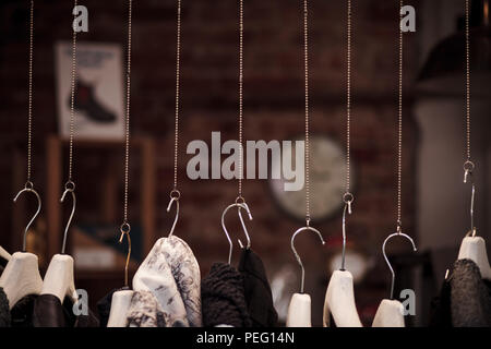 Many clothes hanger on chains with dark background in a shop - Stock Photo